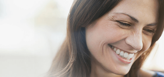woman with eye wrinkles and smile lines smiling looking down