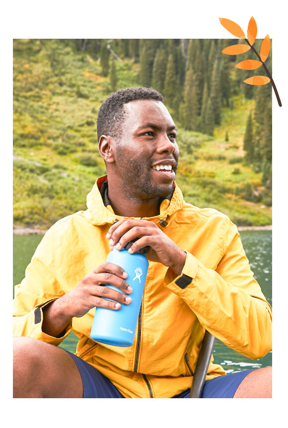 Photo of a smiling man holding a hydroflask water bottle